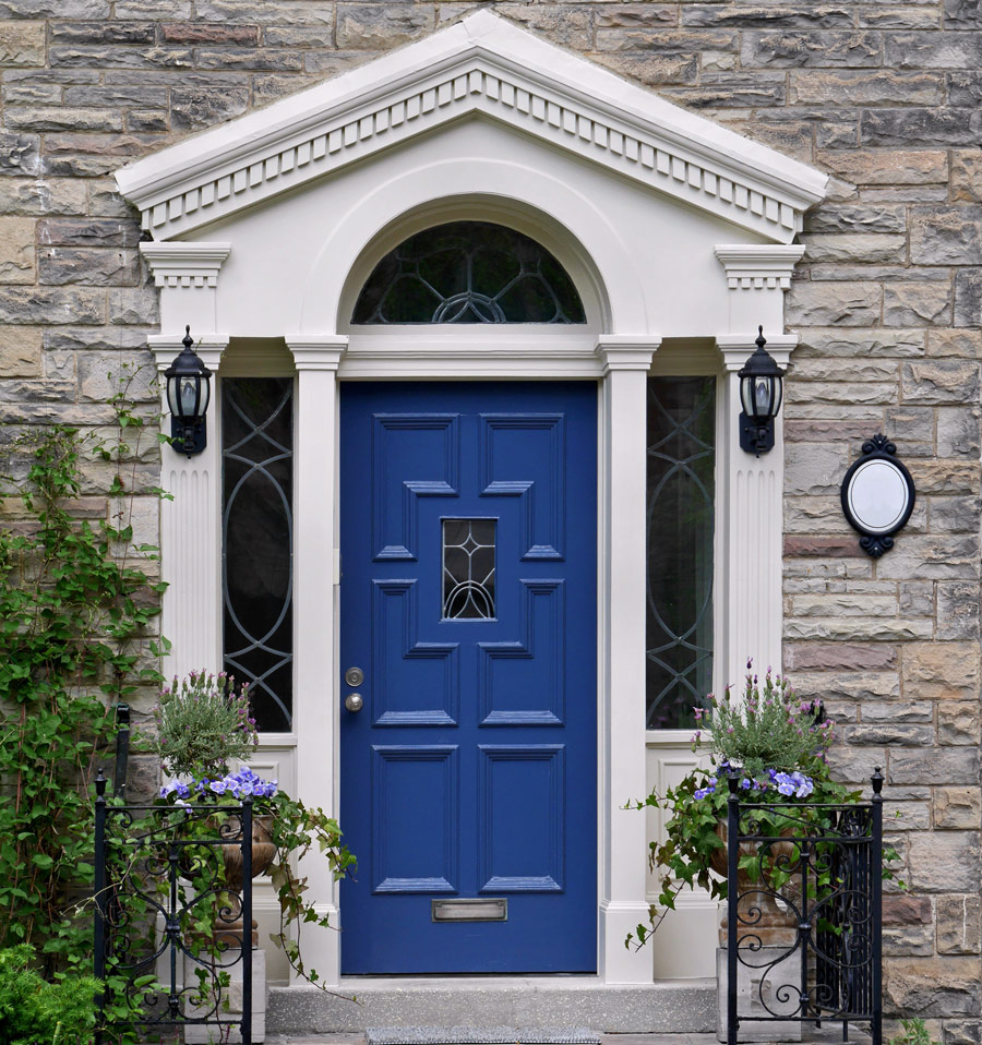 Front door blue with bushes and brick wall