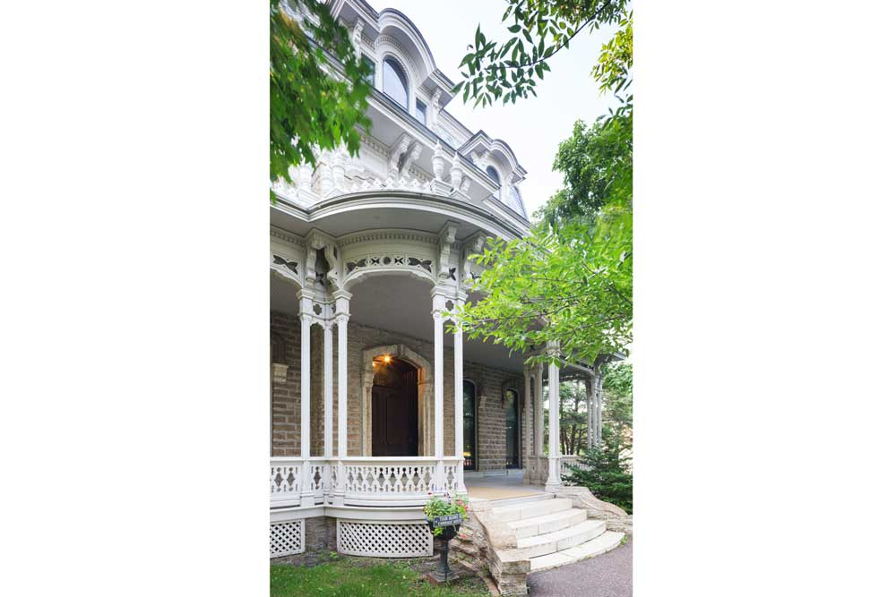 The entryway into the Alexander Ramsey House shows white Victorian architecture with brick incorporated.