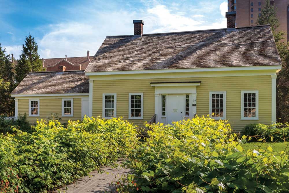 The frontside of the Ard Godfrey house. A charming home that is painted yellow with bushes lining the walkway up to the front door.