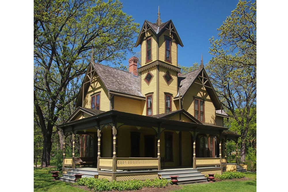 The Burwell House. It's painted yellow, features a wrap-around porch and a tall tower.