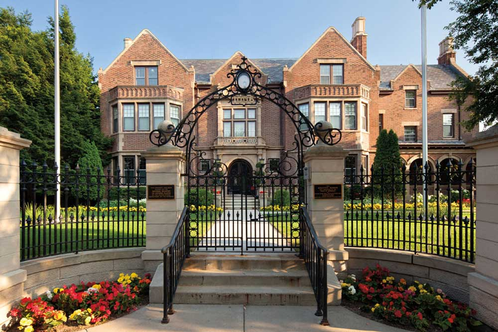 A view from the sidewalk in front of the Governor's Residence. Behind the fence is a large multi-story, symmetrical red brick mansion. Large windows adorn the front.