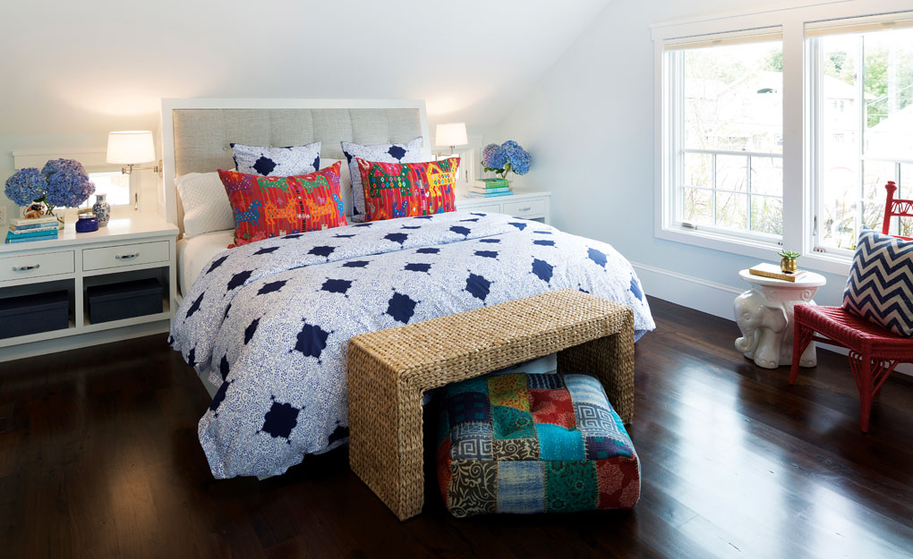A master bedroom with sloping ceiling features a king size bed flanked by matching white nightstands. A wicker bench sits at the foot of the bed, and a red chair sits next to the large windows.