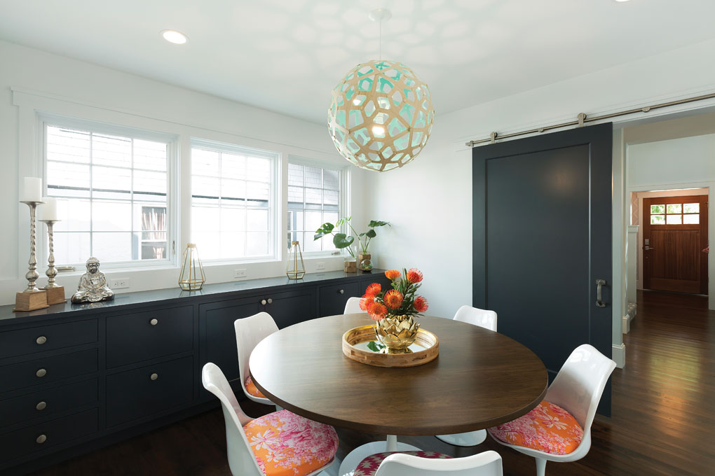 A dining room that features vibrantly-colored seats, a built-in storage area and sliding barn door that allows for privacy.