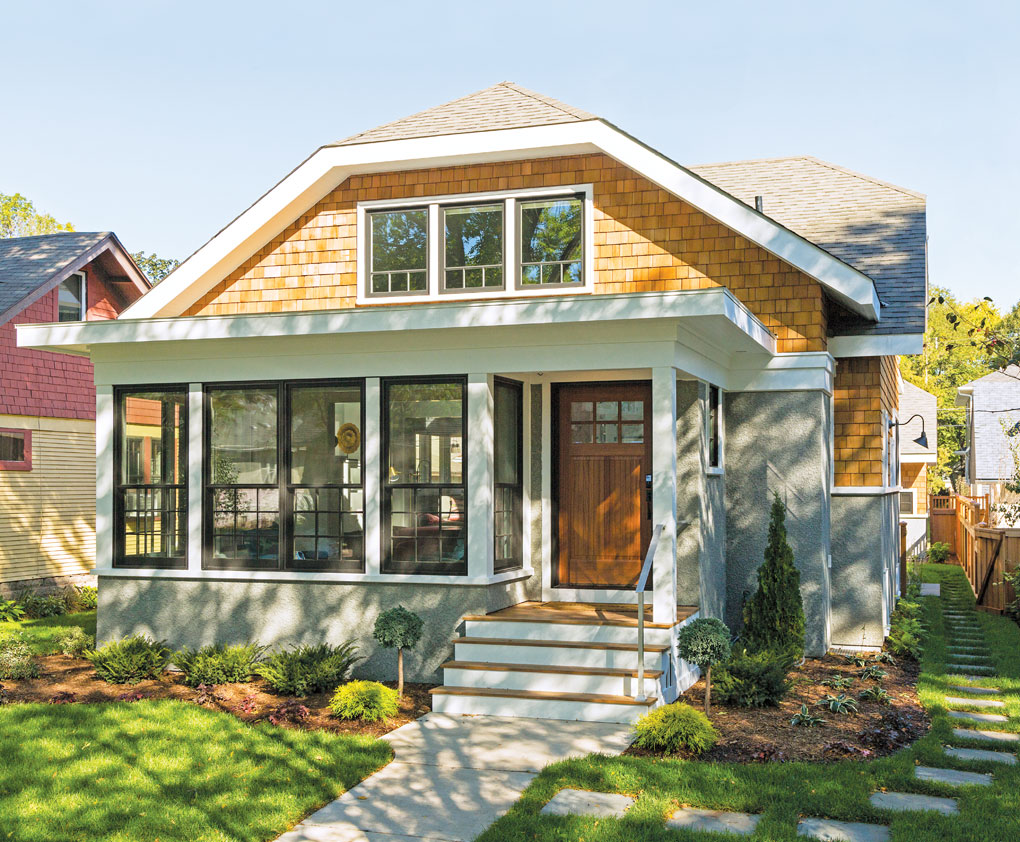 The facade of a bungalow-style home in St. Paul on a sunny day accented by green grass and landscaping.