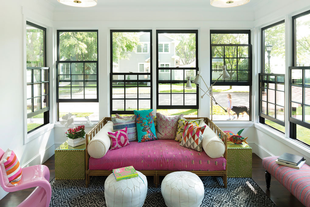 The front porch features large windows that look out onto the sidewalk and street. The inside is accented with a pink couch with colorful pillows, a pink chair and bench.
