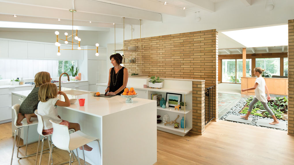 The owner of the home prepares a snack for her daughters as they wait at the counter. A third daughter is walking in the indoor atrium in the background.