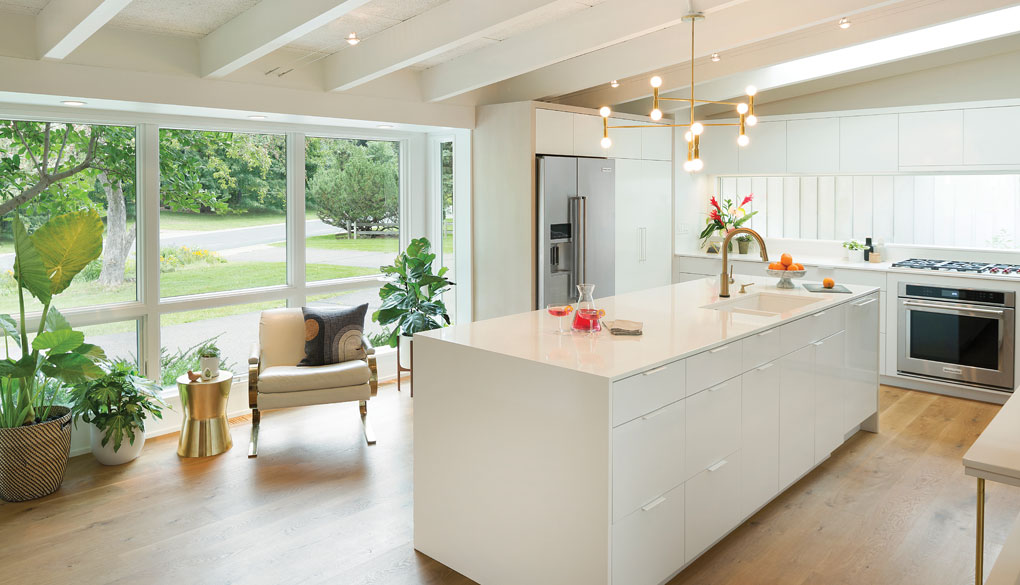 A sleek, updated white kitchen with large windows flanked by plants looks out at the driveway and green surroundings.