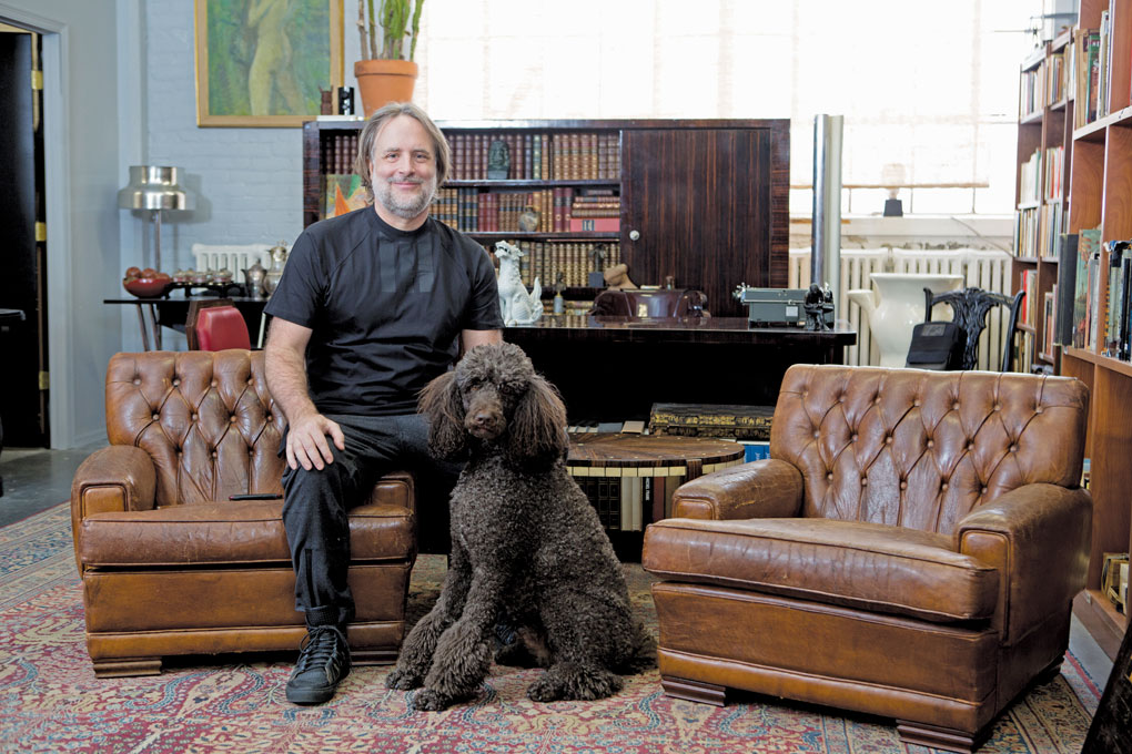 Peter Dyste sitting in a living room on a couch with his dog.