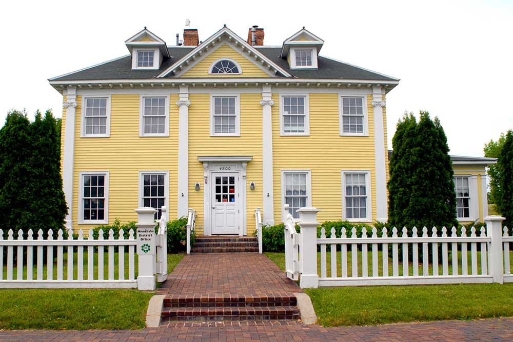 The frontside of a Longfellow House shows a white picket fence outside of a large, two-story, symmetrical yellow home. A brick path leads up to the white front door. Each side of the home features two windows on each story.