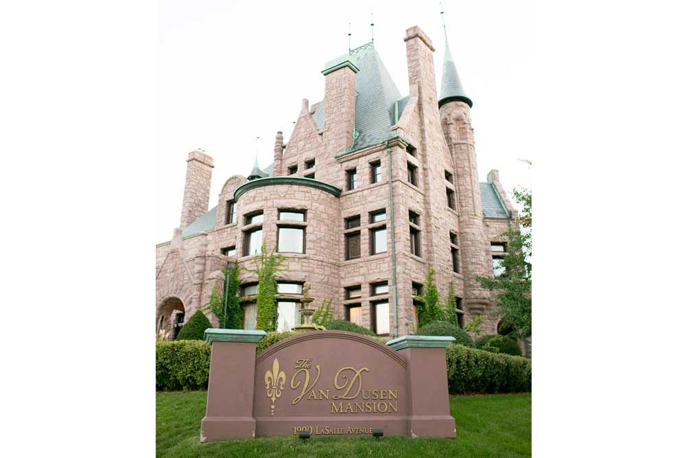 The Van Dusen Mansion is a red stone castle with cylindrical towers capped with green, pointed roofs.