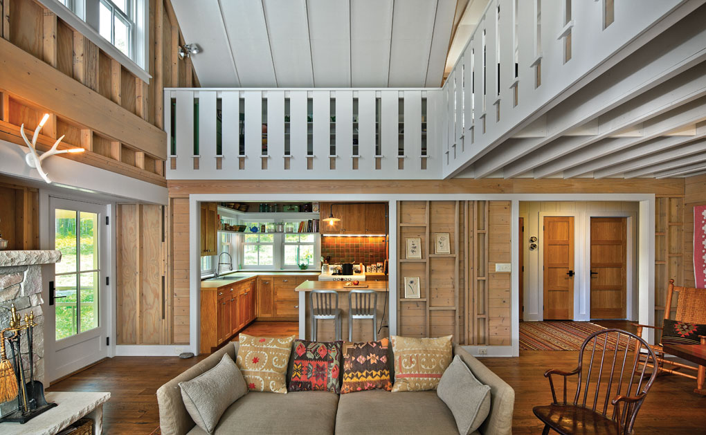 A cottage living room shows hard wood floors, wooden walls, and an overlooking loft.