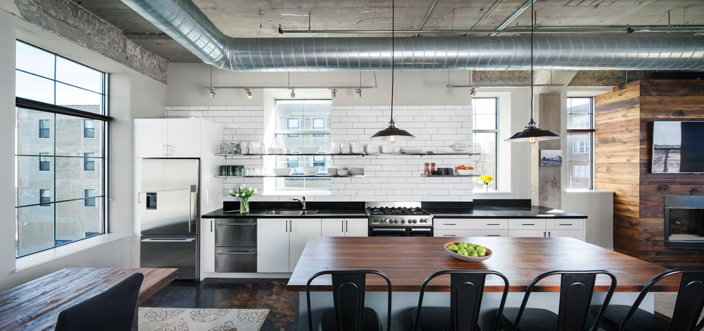 A sleek and modern kitchen designed by Christine Albetsson features white cabinetry, black countertops, a white subway tile backsplash and stainless steel appliances.