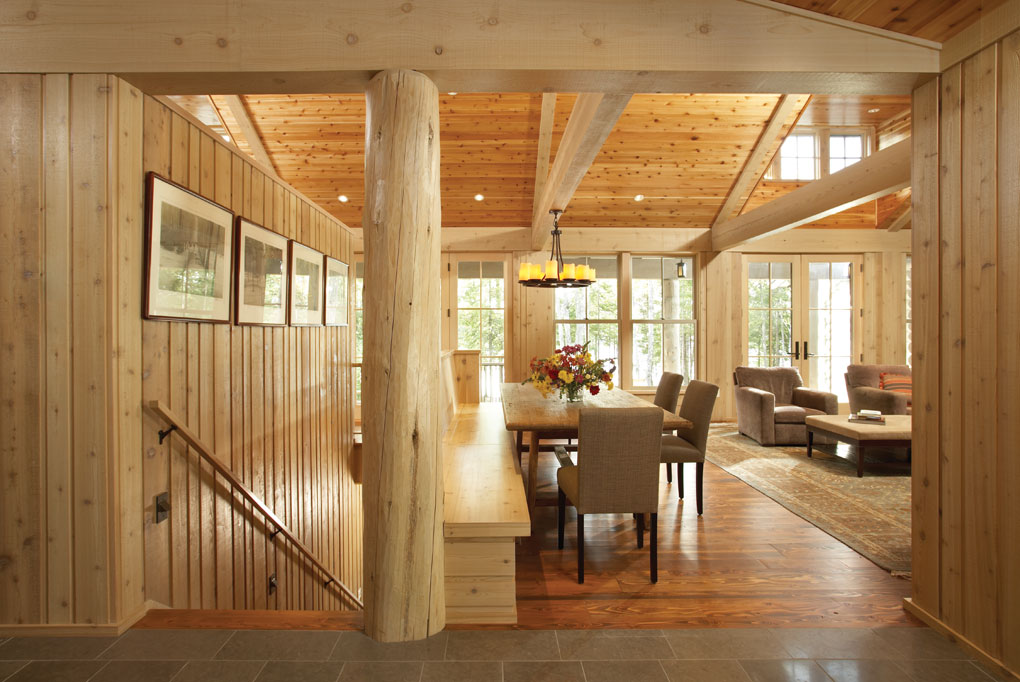 Log and lumber beams, hardwood floors and a wooden ceiling highlight this living room.
