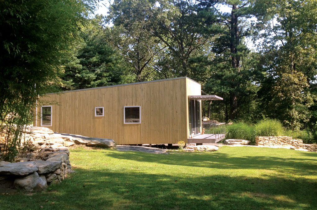 The exterior of a two-room guest house shows opaque stained pine boards and a patio with an overhang. A forest sits behind it.