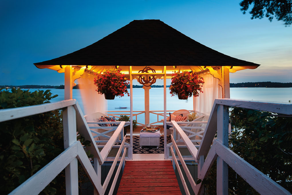 The top level of the Abbott Boathouse shows a cozy gazebo with hanging potted plants that looks out onto Lake Minnetonka.
