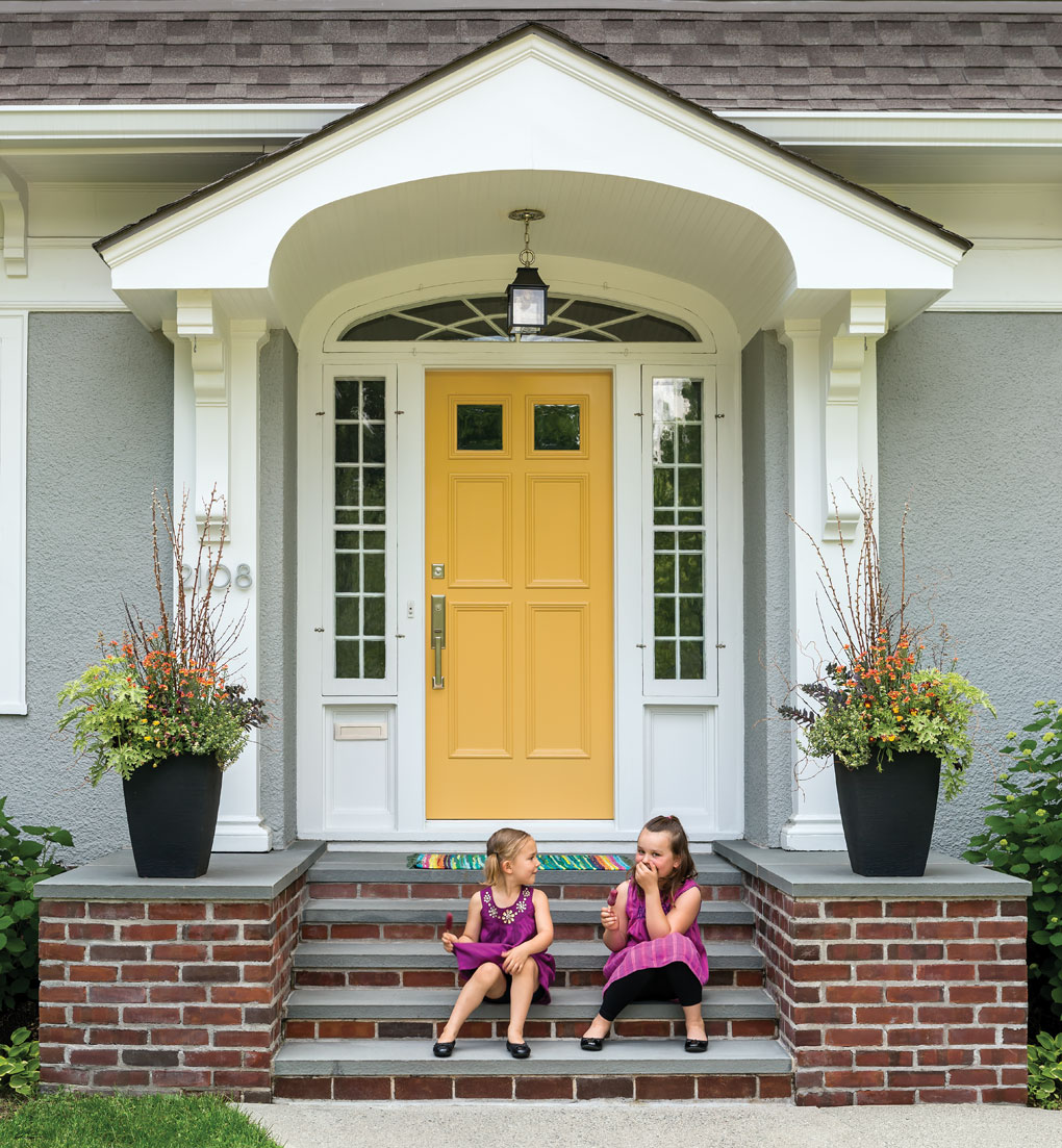 Two young girls having fun sitting on the front steps of their house.