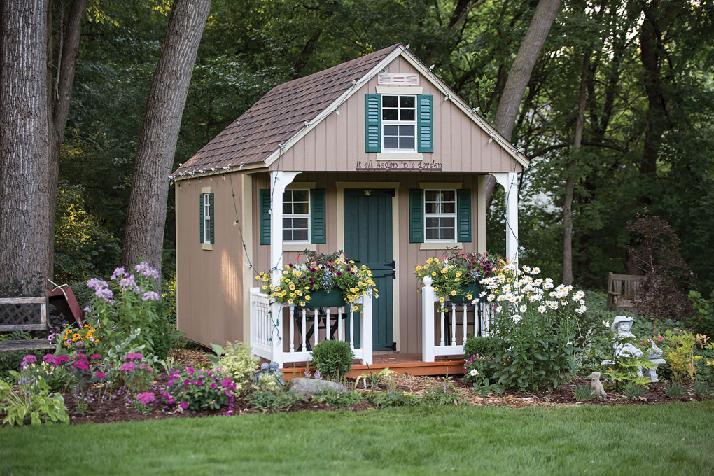A quaint gardening shed with white railings and green shutters.