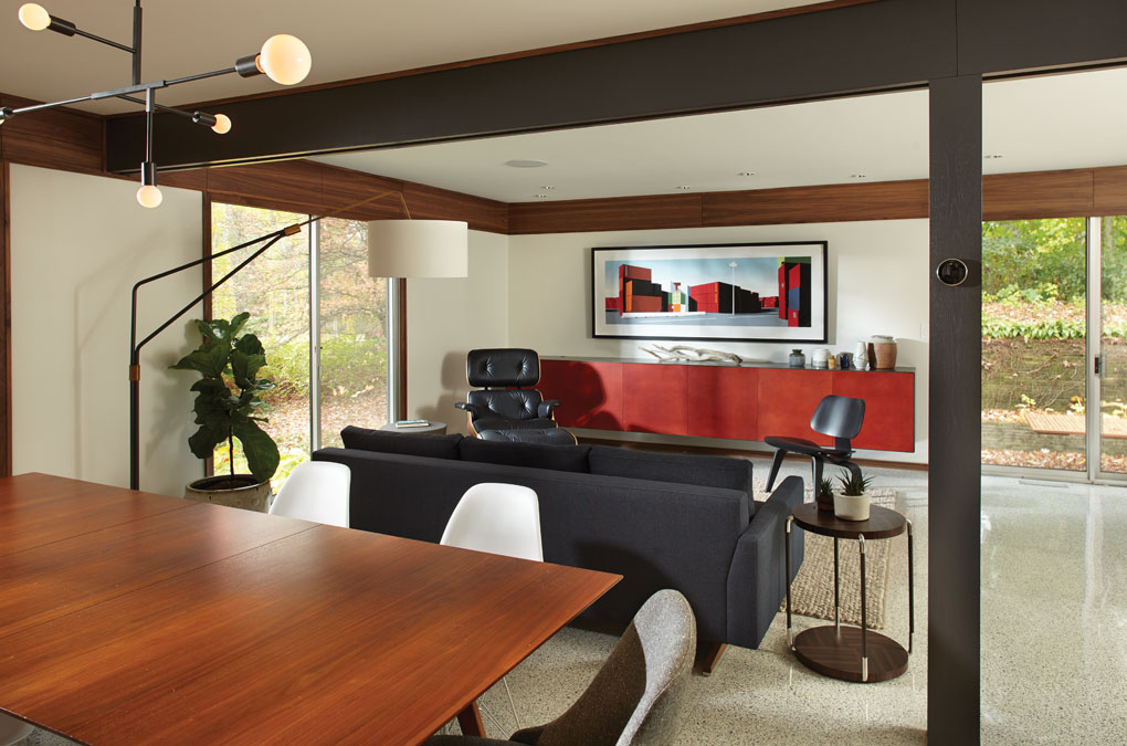 After a remodel, the new living room features a sofa, chairs, a painting on the wall, and a red shelf for displaying other decor.