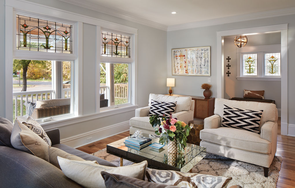 A vintage-style living room with chairs and a sofa surrounding a coffee table. Broad windows with restored stained glass open up to an old-fashioned front porch.