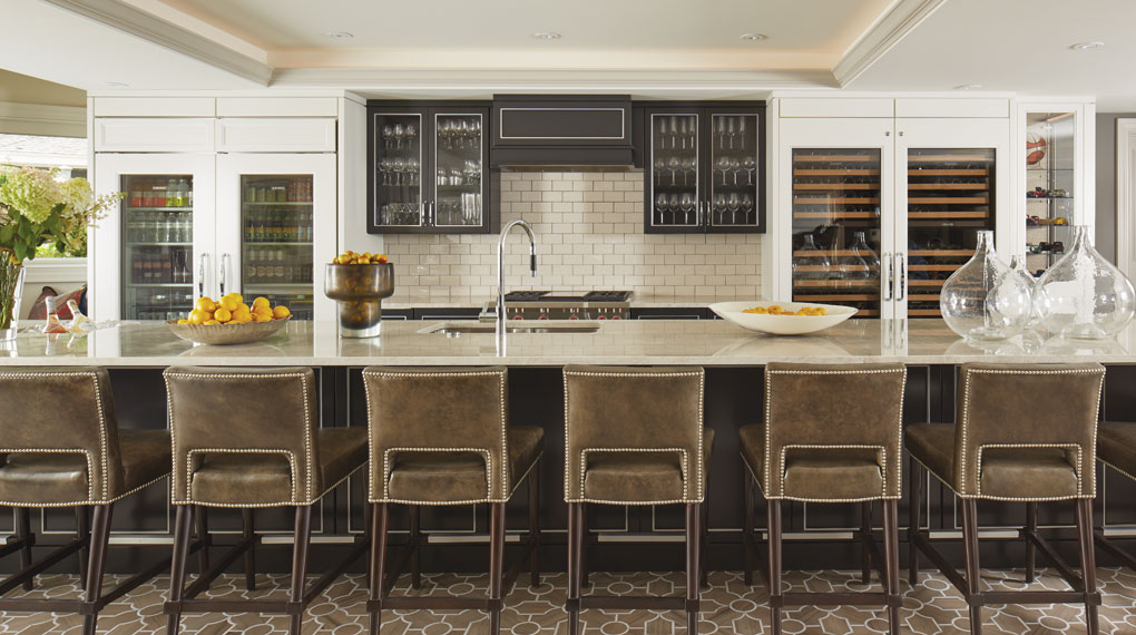 A 20-foot-long bar topped with polished quartzite. Behind it sits storage for wine, soft drinks and other beverages in black satin-enamel cabinetry with a ceiling-height subway tiled backsplash.