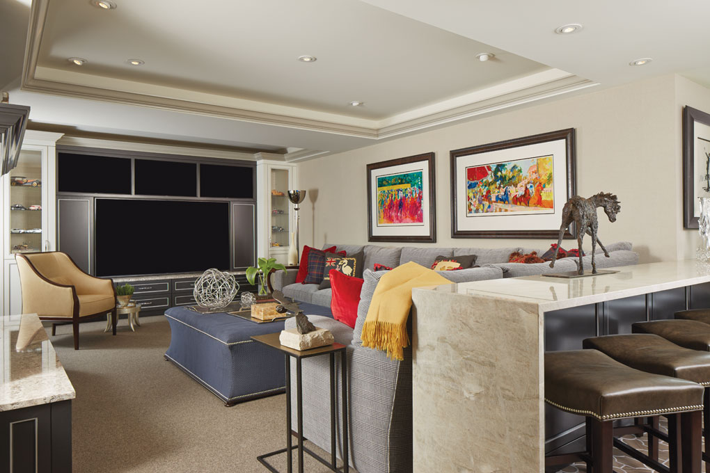 A seating area for entertaining is made up of a large sectional sofa with footstool, chairs and four TVs set in large entertainment stand.