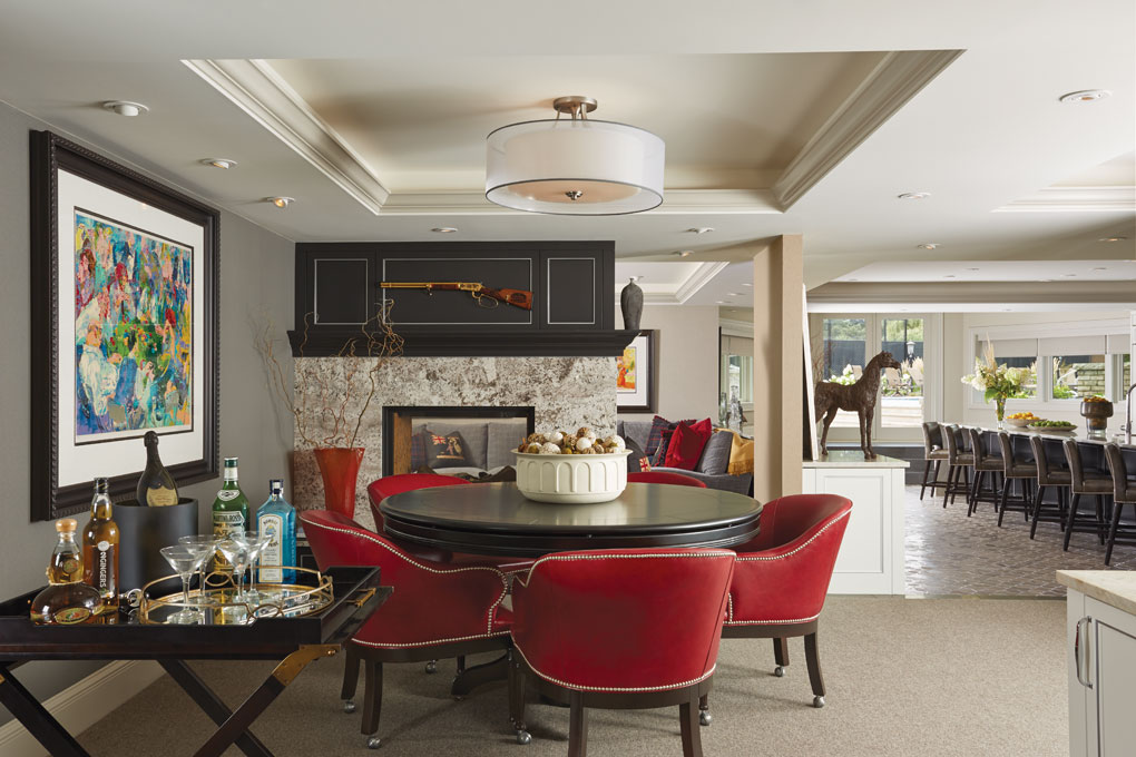 A room dedicated to poker features a butler tray with various alcohol next to a dark, round table surrounded by red leather chairs. In the background is a kitchen and living room.