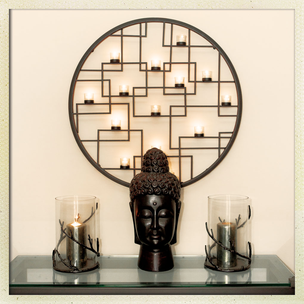 A tea-light candle sconce and Buddha head welcome guests at Jane and Daniel Greens' entryway.