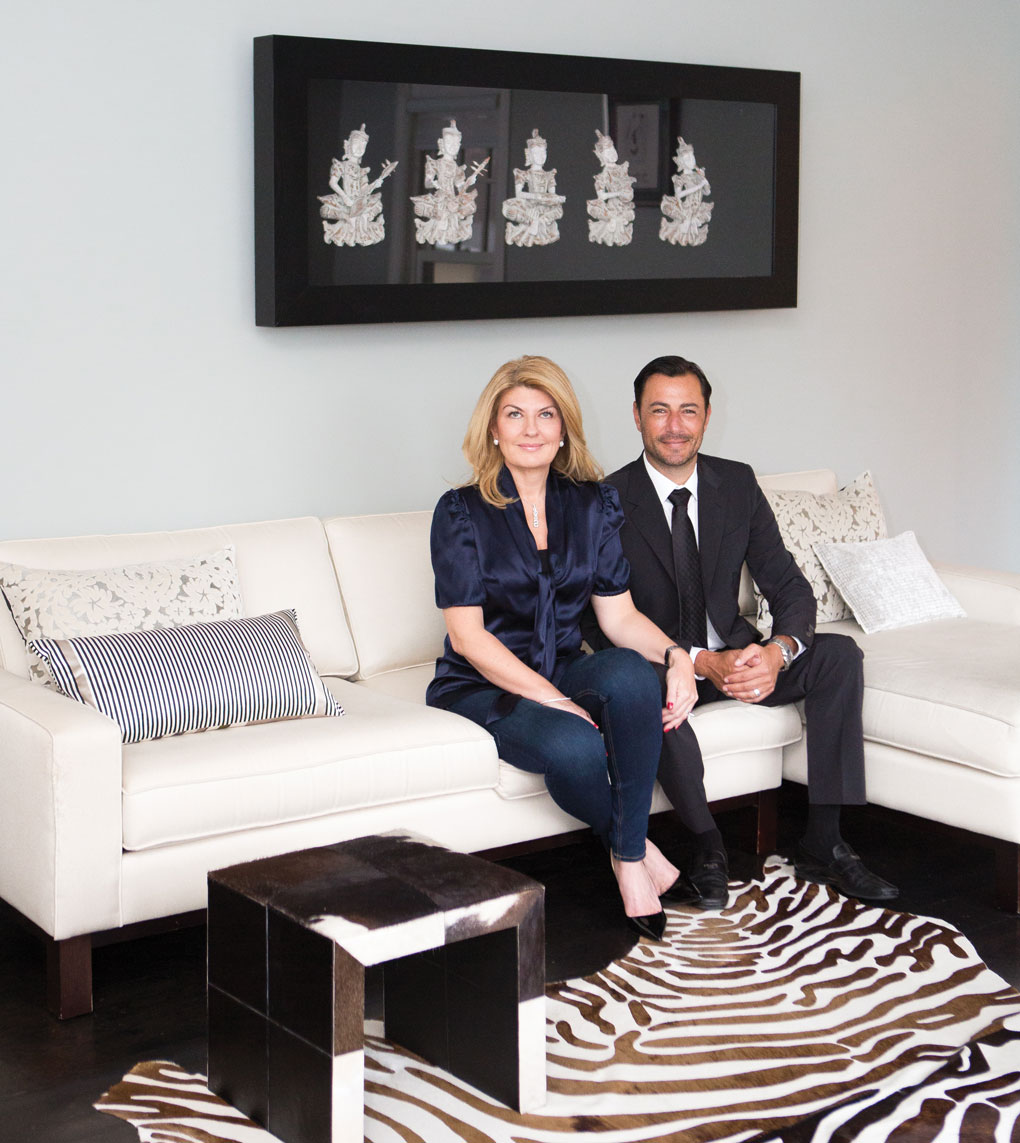 Daniel and Jane Green sit on a white sofa inside their home.