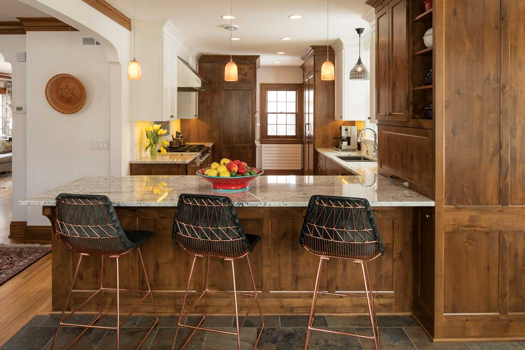 A kitchen featuring wood cabinetry, tile flooring and high chairs surrounding the countertop.