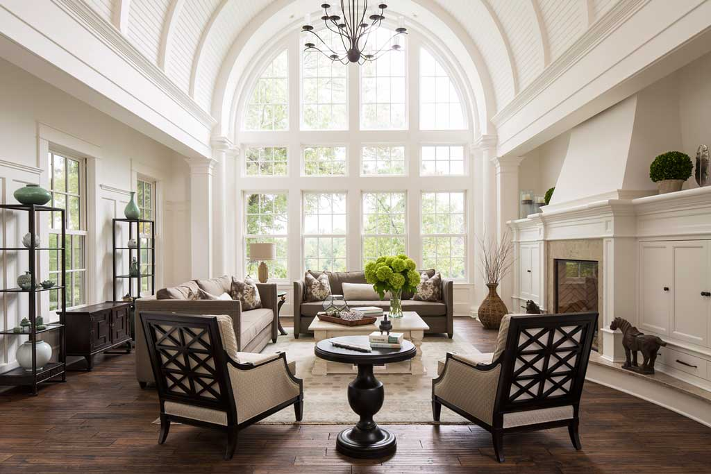 A sitting room designed by Nan Sloan and Kate Regan Allied ASID shows a large, open, white room with dark wood floors. In the center of the room is a cream colored coffee table surrounded by sofas and chairs, and the far side of the room is made up of floor-to-ceiling windows.