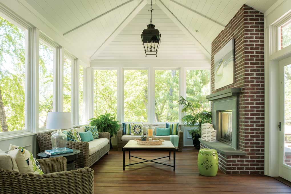 A living room built by Rehkamp Larson Architects featuring wicker furniture and a red brick fireplace.