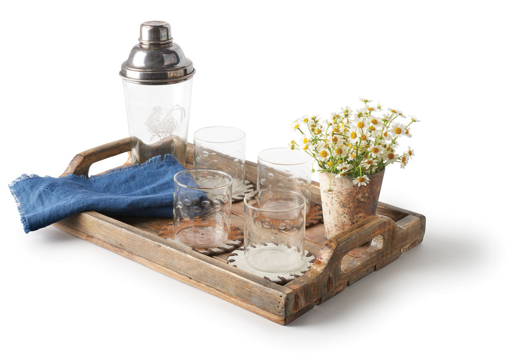 A tray holding an antique cocktail shaker, glasses, coasters, linen indigo napkin, large Sassi votive and tray.