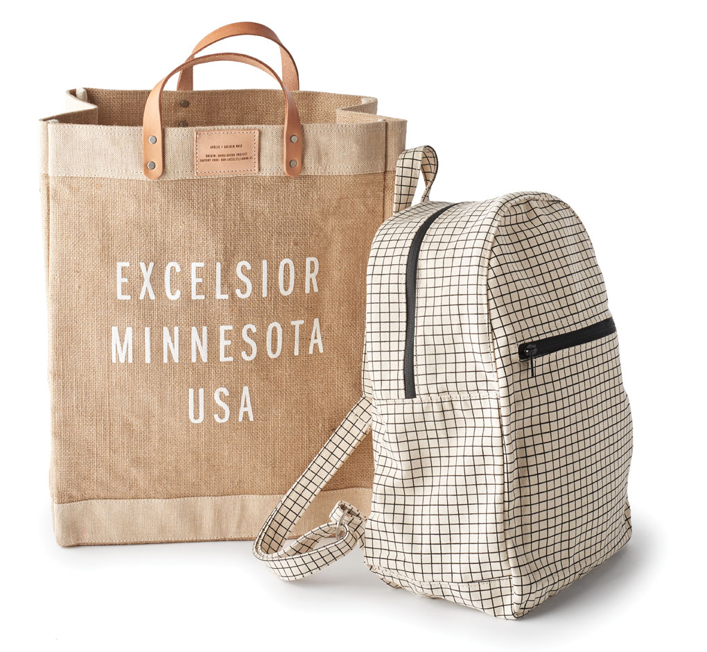 A Baggu zip backpack sits propped against an Excelsior, MN bag