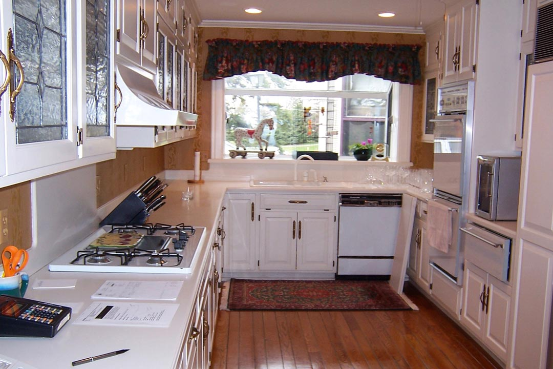 A kitchen before it was remodeled shows outdated appliances and a cramped space.