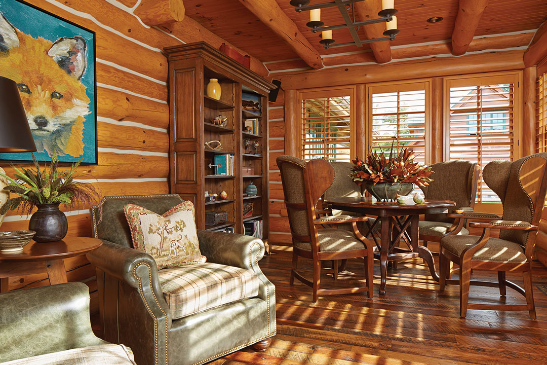 A cabin living room with hardwood floors, log walls and wood ceiling.
