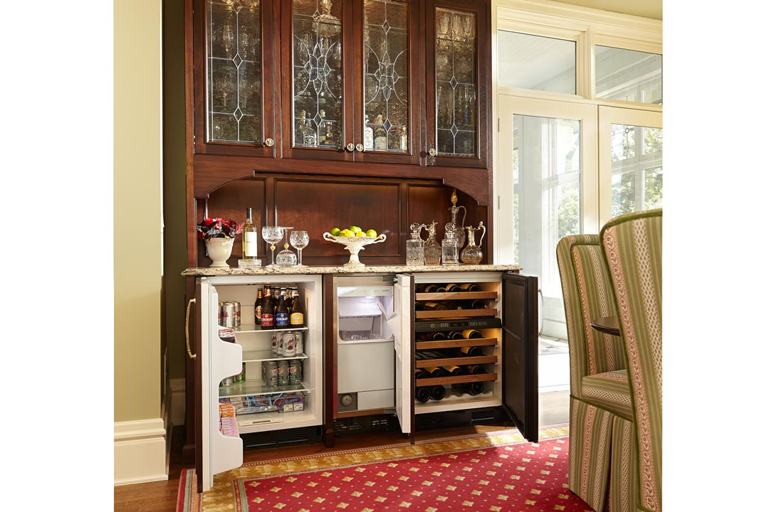 A large, wooden cabinet opens to reveal a hidden fridge and wine cooler.