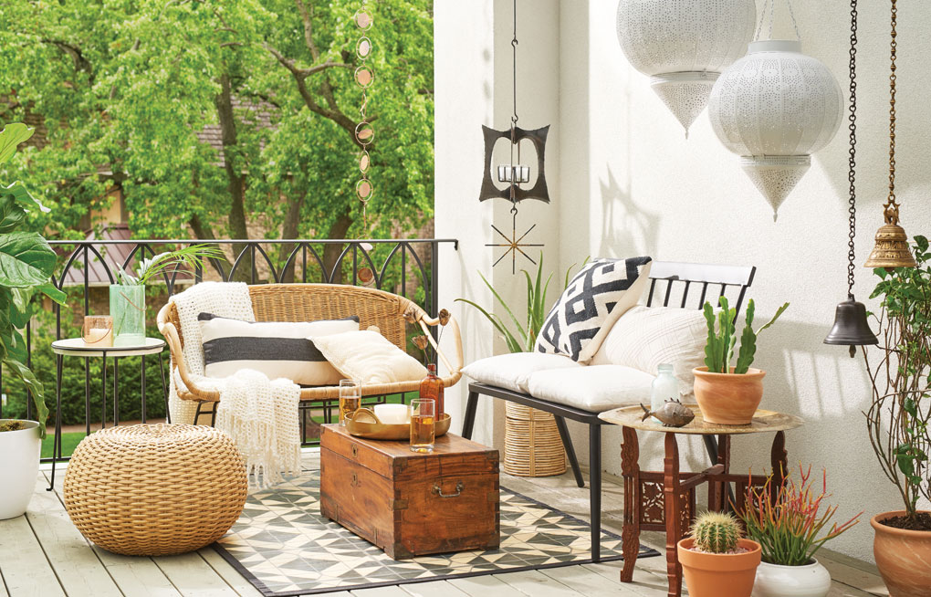 A patio furnished with wicker furniture, stands, hanging candle chandeliers and more.