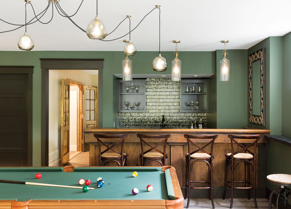 The lower-level bar, also a vintage find, gets a touch of glam from its lighting and glass-tile backsplash.