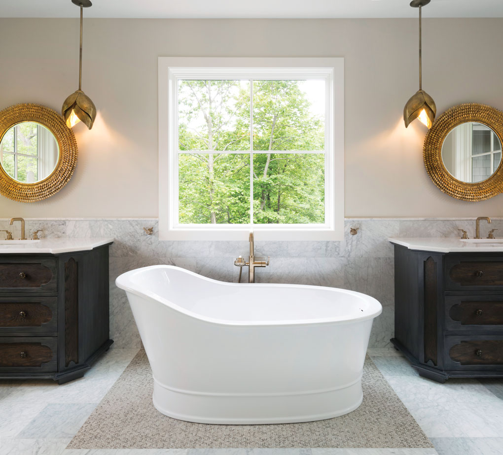 The master bath, spotlights a soaking tub and dual vanities with Art Deco-style lighting.
