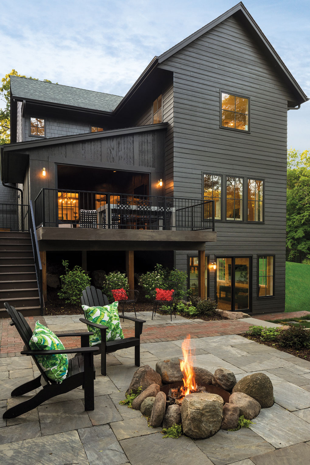 A stone fire pit accents a brick patio.