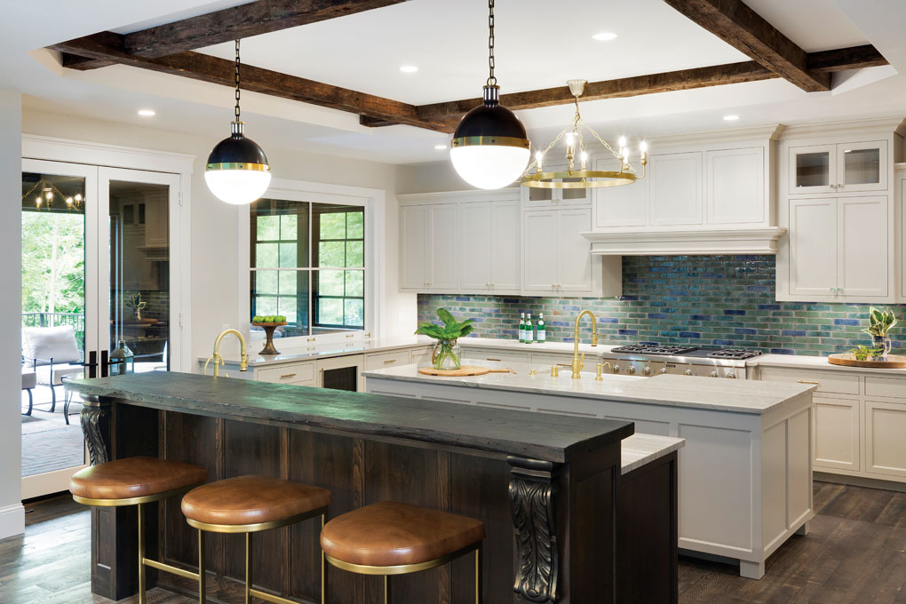The kitchen includes two islands—one with a baking station and mixer lift. Quartzite tops the working surfaces, while a backsplash of handmade tiles offers earthy contrast.