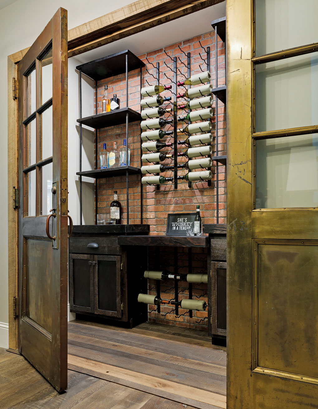 Around the corner from the pub is a wine and bourbon cellar and a tasting area. These patinaed brass doors, salvaged from a city hall, inspired the brass used throughout the house.