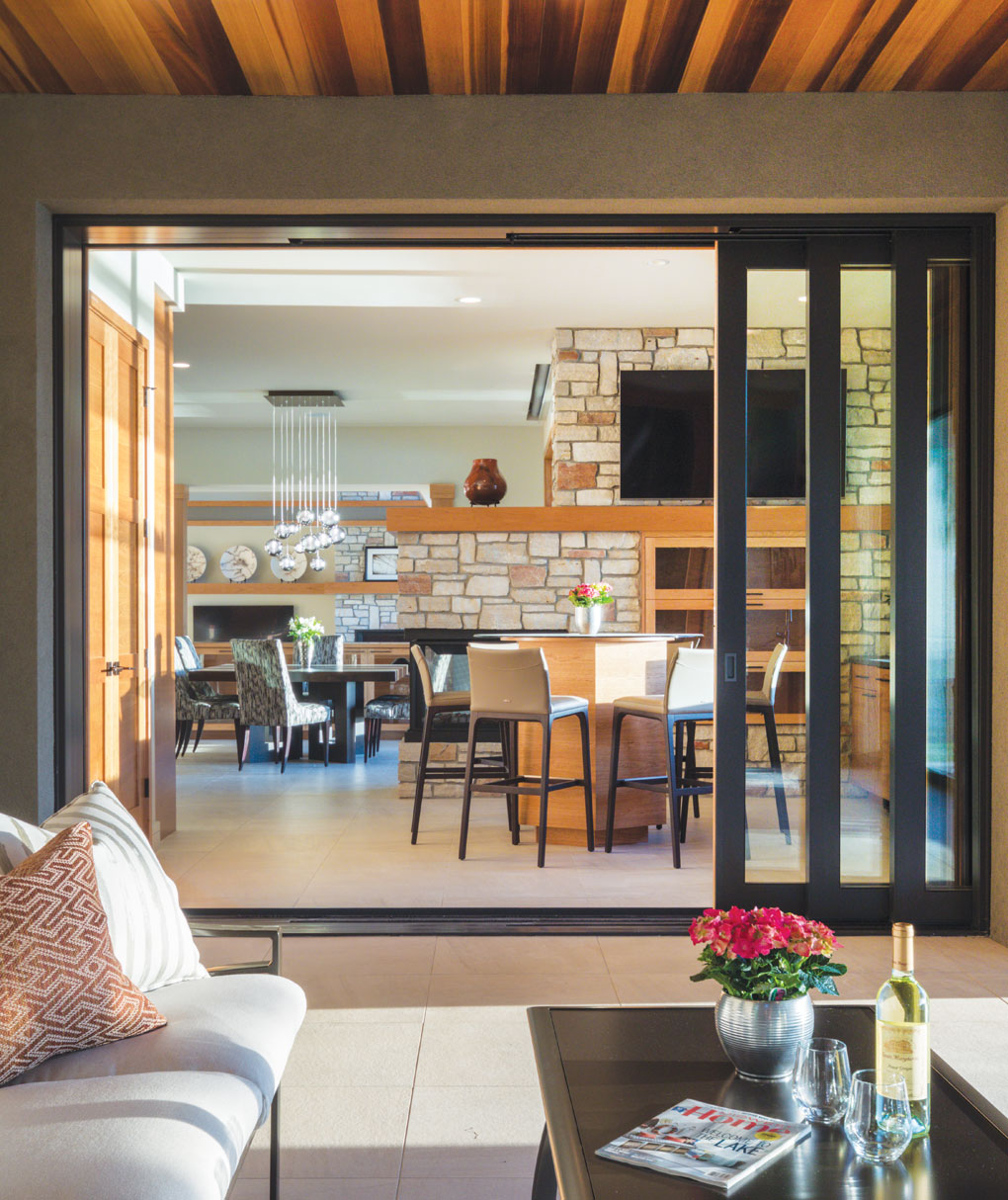 A three-sided Chilton stone fireplace divides the bar and dining area, while pocket doors disappear into the wall between house and screen porch.