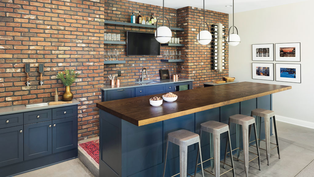 The lower-level entertaining space features a 12-foot bar made from a tree felled on the property and a built-in beer tap.