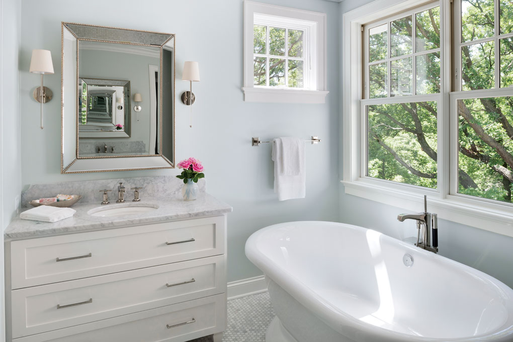 A white bathtub and vanity with a marble countertop are set next to a window overlooking some trees.