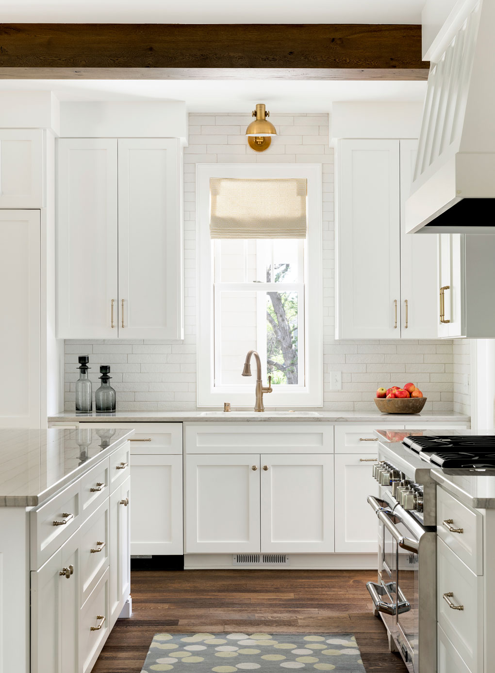 A kitchen with all white cabinetry, a subway tile backsplash and marble countertops.