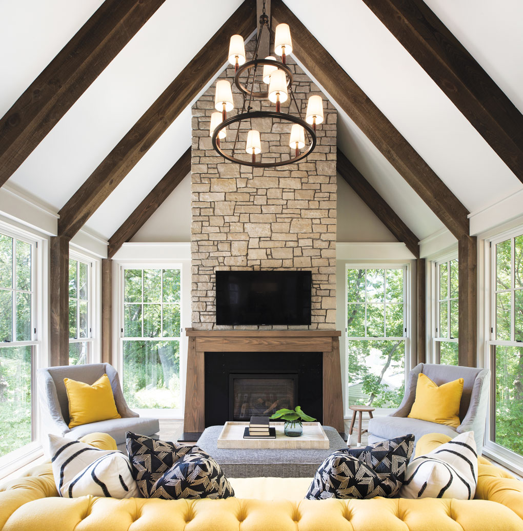 """A year-round porch, dubbed the """"Minnesota Room,"""" creates an outdoorsy vibe with its timbered beams, stone fireplace, and double-hung windows on three sides."""