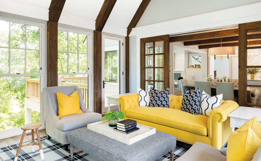 A porch with exposed timber beams that line the ceiling, and a couch and set of chairs surround a fabric coffee table.