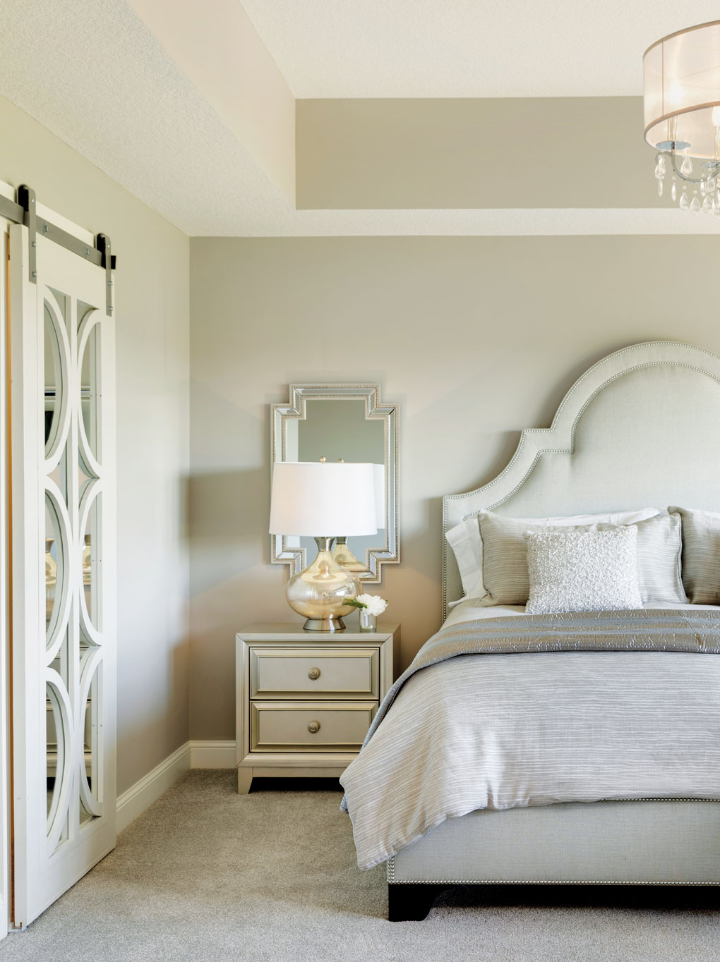 A master bedroom with a large bed and chandelier hanging overhead. Adjacent is a walk-in closet with sliding door.