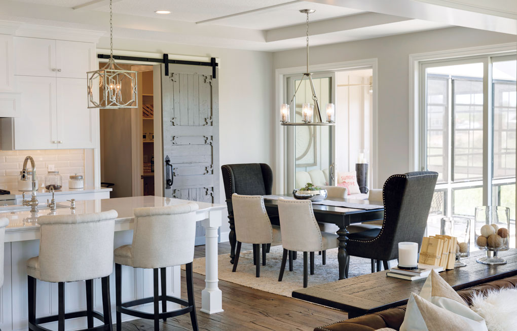 The kitchen is adjacent to a dining table, and both spaces are separated by a sliding barn door which hides a pantry.